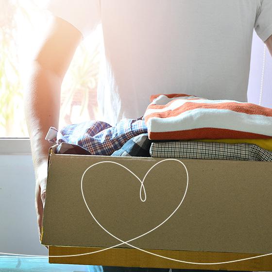 Um homem de camiseta branca, segurando uma caixa de roupas. Por cima da imagem, um desenho de coração.