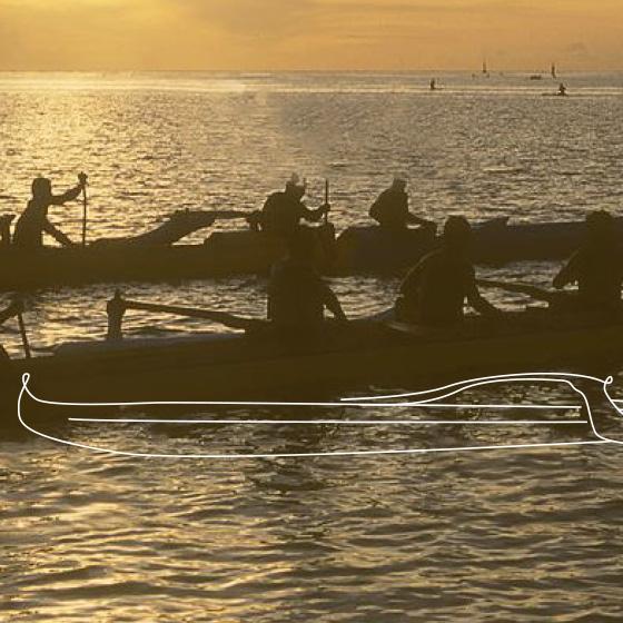 Duas canoas em um rio, com aproximadamente 4 pessoas em cada canoa, ambas estão remando. Por cima da imagem, um desenho de canoa.